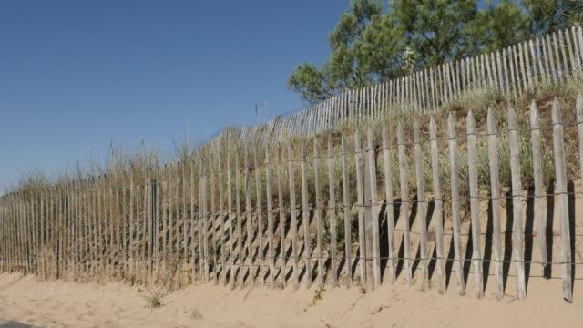 vídeos y material grabado en eventos de stock de frontera natural de mar hechas de tablones a inclinación lenta playa - valla límite