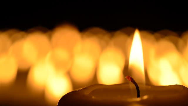 A sea of candles Candle in front of many defocused candleflames creating a spiritual atmosphere and in remembrance of loved ones zen like stock videos & royalty-free footage