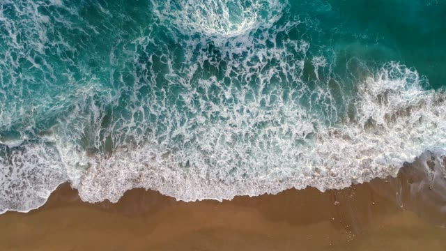 Sea or ocean surf wave. Foamy ocean waves rolling and coming on a sand beach. Aerial top down shot, 4K