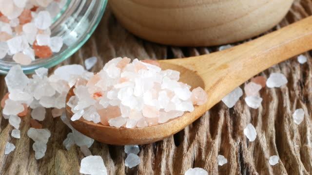 sea salt and himalayan. crystals of salt on old wood table. - salt video stock e b–roll