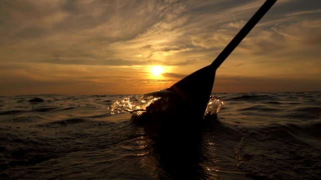 SLOW MOTION: Sea splashing into camera when pushing paddle blade through water video