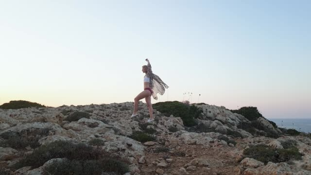 havet sommarsemester. ung smal atletisk kvinna i bikini och pareo går på stenig terräng mot bakgrund av det blå havet vid cape greco vid solnedgången - sarong bildbanksvideor och videomaterial från bakom kulisserna
