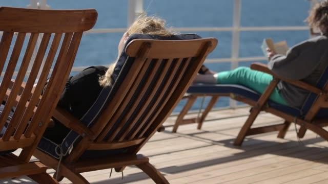 海の旅と客船リラックスします。大西洋横断クルーズ中のデッキチェアでリラックスの人々。スローモーション映像 - デッキ点の映像素材/bロール