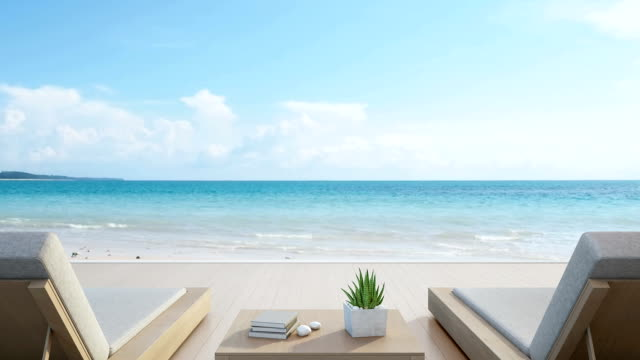 Sea view terrace and beds in modern luxury beach house with blue sky background, Lounge chairs on wooden deck at vacation home or hotel