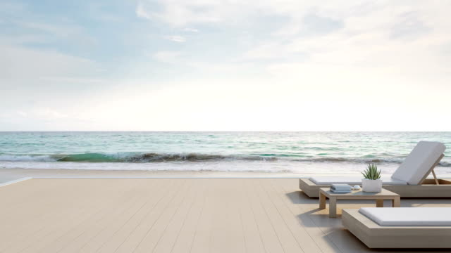 海を望むテラスとモダンで豪華なビーチハウス青空背景に、別荘のウッドデッキのサンラウン ジャーやホテルのベッド - 別荘点の映像素材/bロール