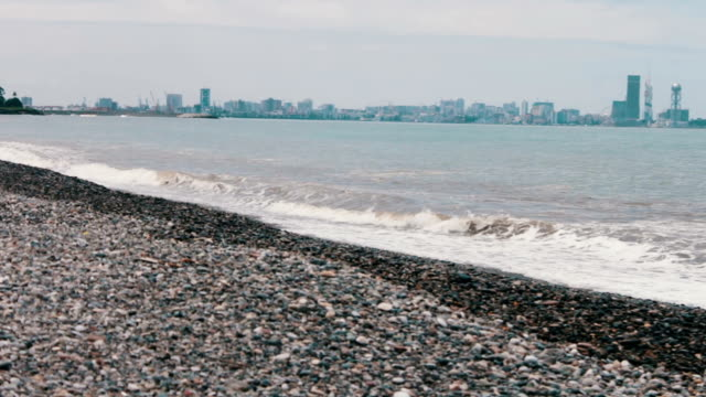Sea waves beat on stony shore on the embankment of the Georgian city resort of Batumi video