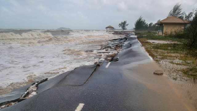 Sea waves caused by a heavy storm hit and destroy a paved road Sea waves caused by a heavy storm hit and destroy a paved road earthquake stock videos & royalty-free footage