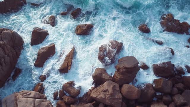 sea waves crashing on the rocks. aerial video shot by a drone.. emerald coast, sardinia, italy. - sardegna video stock e b–roll