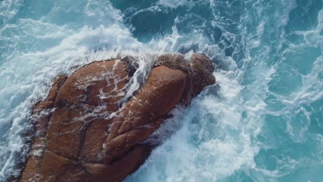 sea waves crashing on the rocks. aerial video shot by a drone. emerald coast, sardinia, italy - sardegna video stock e b–roll