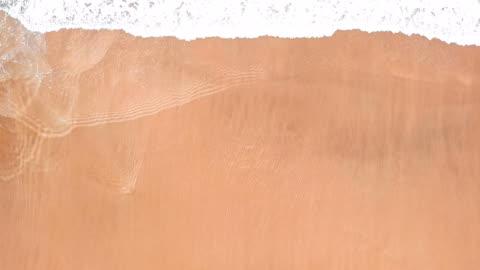vídeos de stock e filmes b-roll de sea waves over sand beach aerial background - areia