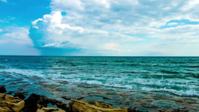 Sea waves splashing on stony beach, low clouds in sky video