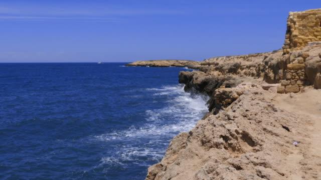 Sea waves splashing on stony coast with fortress on horizon background
