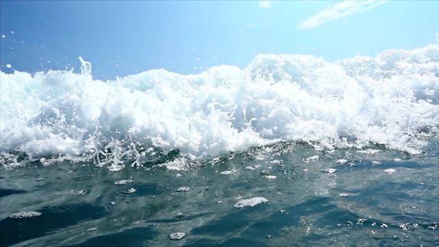 slo mo sea waves splashing over camera - poco profondo video stock e b–roll