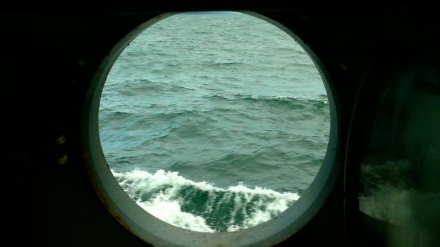 Bидео sea waves through the porthole of a ship (slow motion)