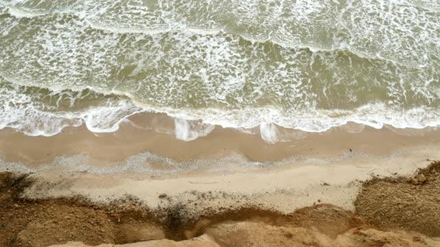 stockvideo's en b-roll-footage met zee met golven onder de heuvels. natuurlijke kust landschap. berg met oceaan breze. - duurzaam toerisme
