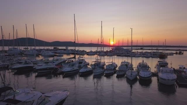 vídeos de stock, filmes e b-roll de mar de iates no pôr do sol laranja, vídeo de drone k 4 - marina