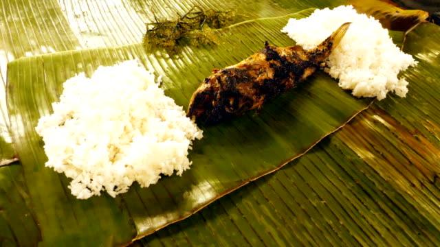 piatto di pesce servito in una foglia di banana in un ristorante - filippino video stock e b–roll
