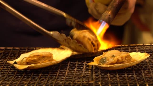 vídeos de stock, filmes e b-roll de frutos do mar vieiras grelhadas no mercado de peixe no japão - foco difuso