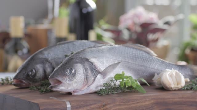 vídeos de stock, filmes e b-roll de filé de robalo de frutos do mar. comida saudável cozinha colorido - cru