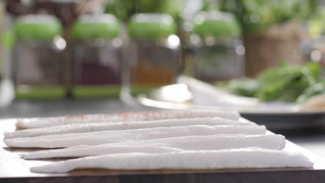 vídeos de stock, filmes e b-roll de filé de robalo de frutos do mar. cozinha colorida - cru