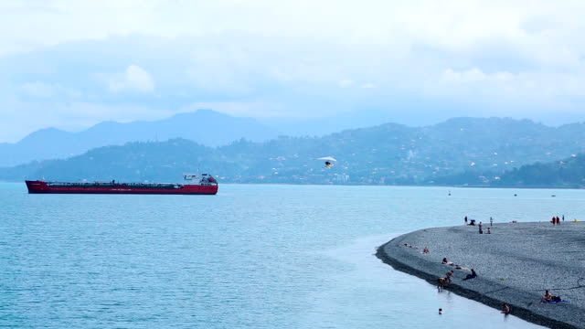 Seafront area with cargo ships and deltaplane in the sky in Batumi, resort city video