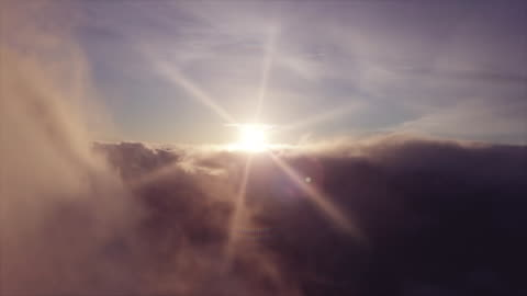 Seamless Aerial Footage in Clouds at Sunrise - Video Looped Drone Shot of a sunrise in clouds, seamlessly looped continuity stock videos & royalty-free footage