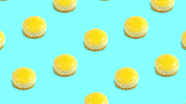 seamless animated pattern with many round desserts of yellow color with biscuits above a cyan background, top view - chrupkie ciasto filmów i materiałów b-roll