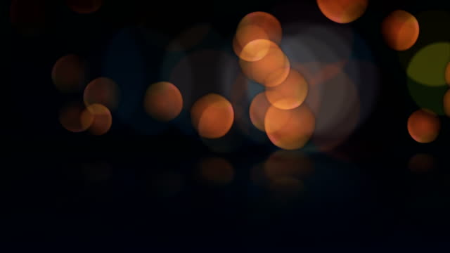 Seamless loop abstract motion background. Animation of bokeh or defocus orange particles and reflection.