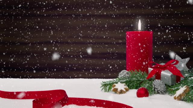 Nahtlose Schleife von einem schönen Schneefall vor ein Weihnachtsarrangement Dekoration auf einem verschneiten Tisch vor einem hölzernen Hintergrund – Video