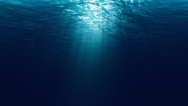 seamless loop of deep blue ocean waves from underwater background, light rays shining through