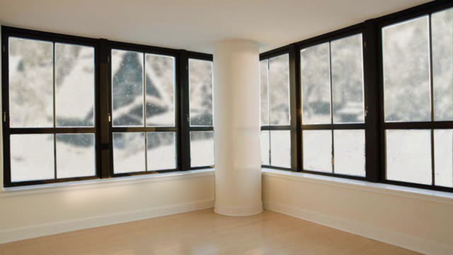 Seamless loopable background of modern living room. Outside the windows there is white snow. Rural landscape behind window. Empty room in house. Snow fall countryside indoors. Christmas eve. Seamless loopable background of modern living room. Outside the windows there is white snow. Rural landscape behind window. Empty room in house. Snow fall country indoors. interior designer stock videos & royalty-free footage