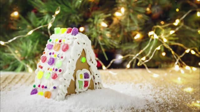 seamless loopable snow on gingerbread house with christmas tree background. holiday concept. cinemagraph - gif filmów i materiałów b-roll