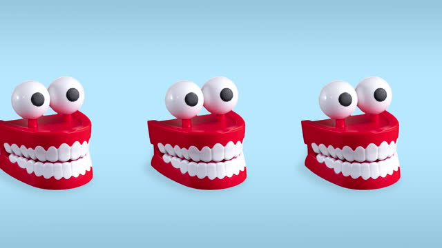 seamless looping animation of one row chattering teeth toys with big eyes on a blue pastel background. plastic red mouths with white fangs is a concept of oral hygiene and healthy teeth