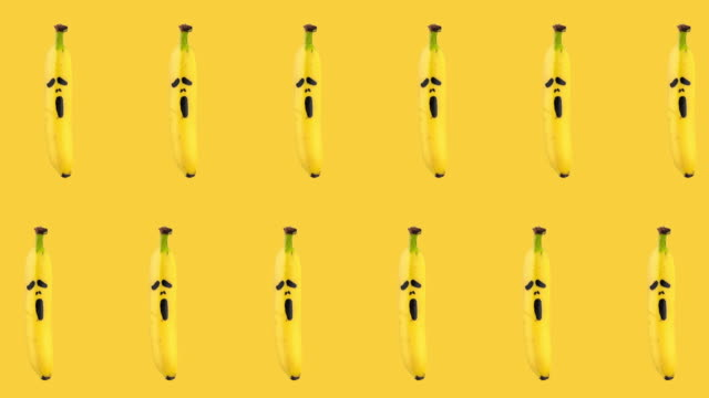 seamless looping animation of two rows of bananas with painted on them scary mask of fear on a yellow background. Halloween concept with copy space