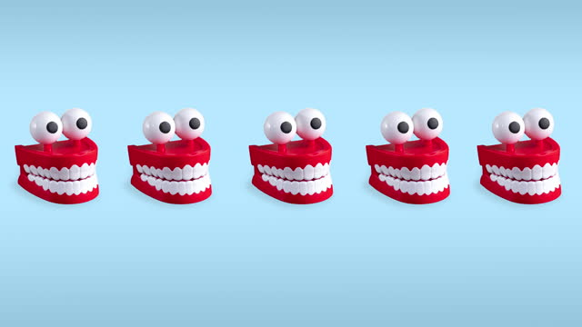 seamless looping funny animation of chattering teeth toys with big eyes on a blue pastel background. plastic red mouths with white fangs is a concept of oral hygiene and healthy teeth