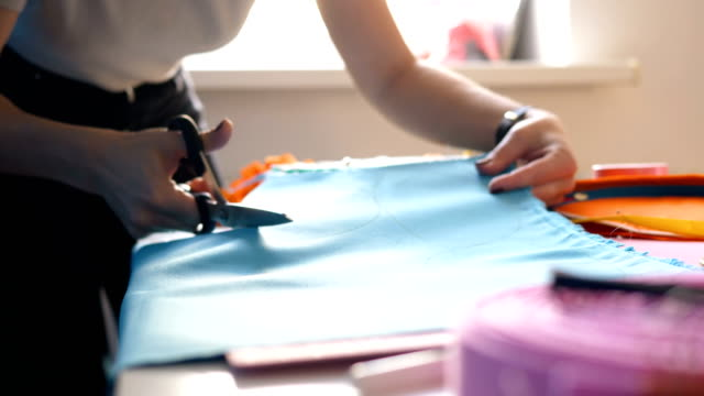 seamstress cuts blue fabric piece with scissors on desk - cucire video stock e b–roll