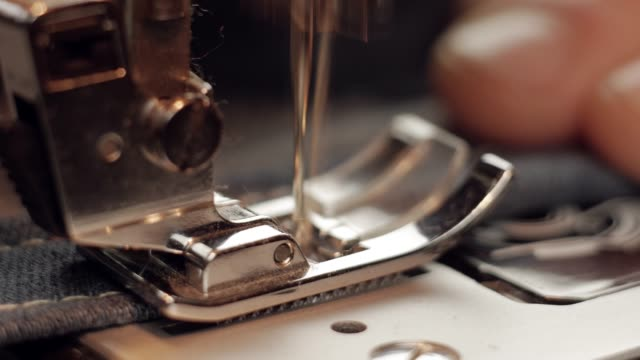 seamstress sewing blue jeans denim on a sewing machine video
