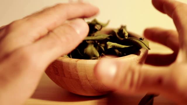 sear mandarin leafs in a wooden bowl - abbrustolito video stock e b–roll