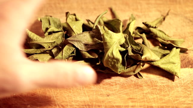 sear mandarin leafs on a wooden table sear mandarin leafs on a wooden table and a human hand mix them seared stock videos & royalty-free footage