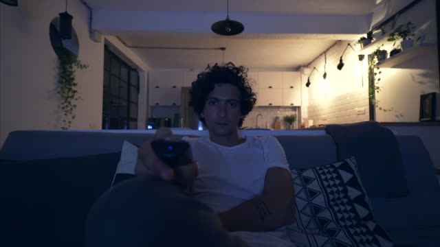 Searching a good TV channel. Man relaxing late in night on the sofa. He is searching a good TV channel to watch. changing channels stock videos & royalty-free footage