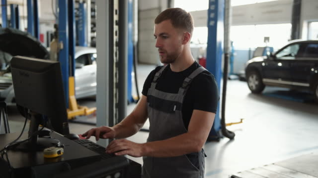 Searching for information. Man at the workshop in uniform use computer for his job for fixing broken car