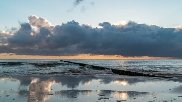 seelandschaft zeitraffer des sonnenaufgangs am strand mit wolken, die sich im wasser spiegeln - ostsee stock-videos und b-roll-filmmaterial