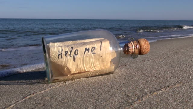 """Seascape with bottle with a message """"help me"""" in  sand"""