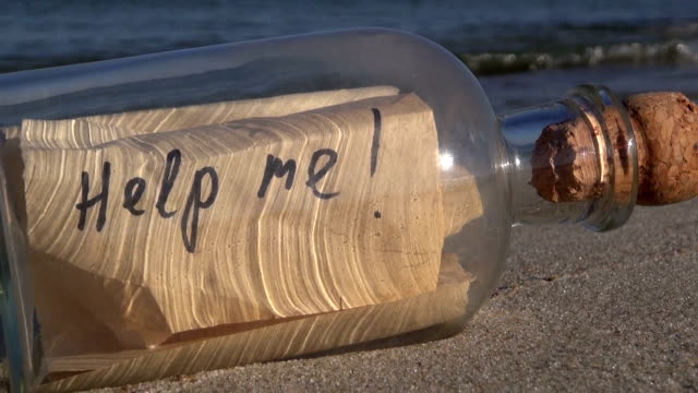 """Seascape with transparent bottle with message """"help me"""" in  sand"""