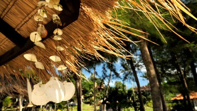 vídeos de stock, filmes e b-roll de um seashell móvel balança com o vento, em uma bela praia da tailândia. - mobile