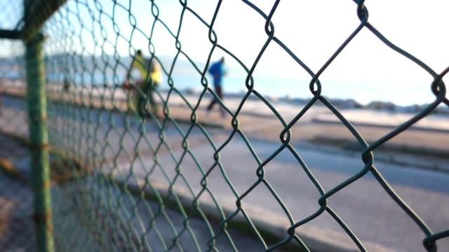 Seaside and People Behind the Metal Fence