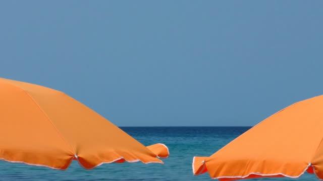 seaside resort sonnenschirme und verschwommene blaue meer hintergrund - sonnenschirm stock-videos und b-roll-filmmaterial