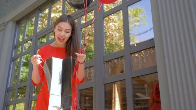 vídeos y material grabado en eventos de stock de temporada de descuentos, adelantos de clientes femeninos en paquete con nuevas compras de tienda de moda durante la venta en negro el viernes - black friday sale