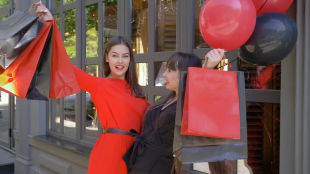 vídeos y material grabado en eventos de stock de temporada de ventas, alegres mujeres agitando compras y riendo después de visitar tiendas con descuentos en black el viernes - black friday sale