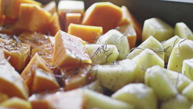 seasoned potatoes and pumpkin ready for baking - węglowodan jedzenie filmów i materiałów b-roll
